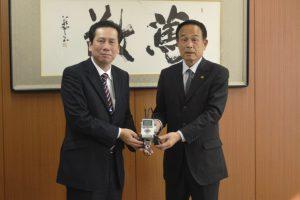 ロボットの組み立てキットを加山市長に手渡す岩下支店長(左)