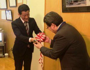 左利き用お玉を手渡す浦上社長(左)