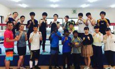 一橋大ボクシング部のメンバーに囲まれる選手と岡川さん(前列左)