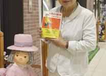店舗の前で自作の人形と石井さん