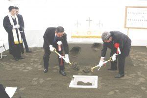 聖書を地中に収める「定礎」を行う佐藤理事長ら