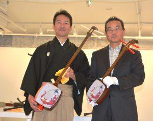胡弓型の三味線を持つ小松社長(右)