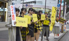 反射素材で作った衣装を着て街頭に立つ学生ら
